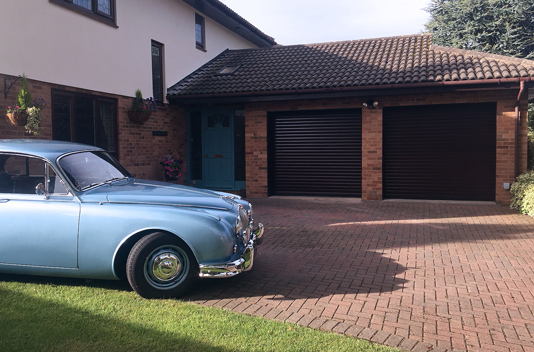 twin roller garage door home with classic jaguar