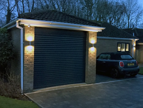 anthracite grey roller garage door with evening lighting