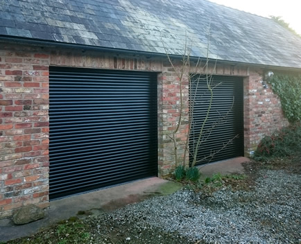 rural conversion with electric roller garage doors in black