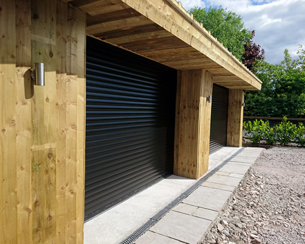roller garage doors in black with timber clad exterior