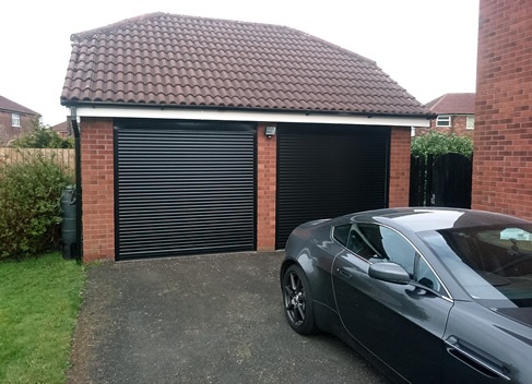 twin roller garage doors with aston martin outside