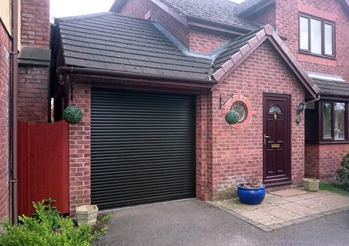 completed install of black finish aluminuim roller garage door