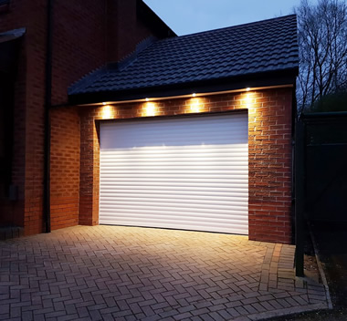 electric roller door in white at night with lights